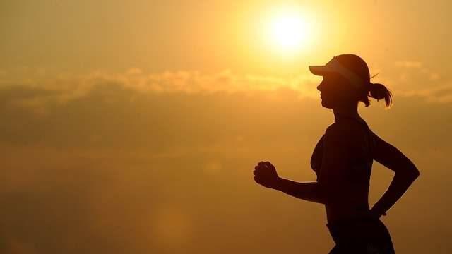 夕日に向かって走る女性